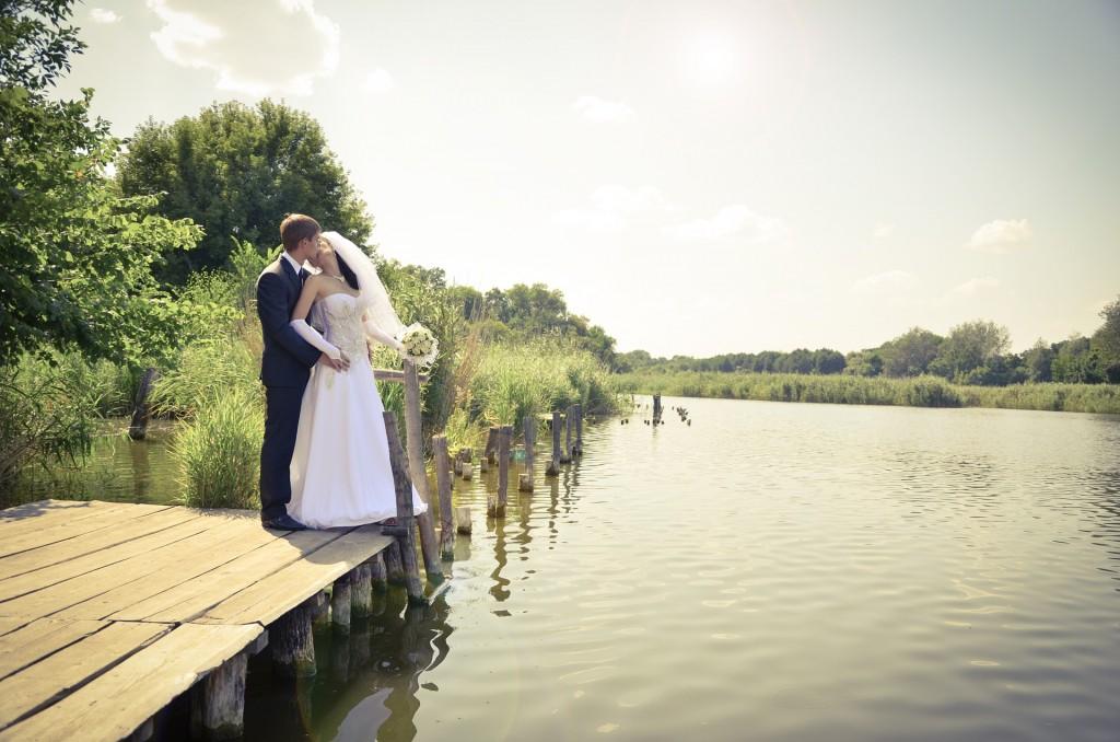 novios,boda sobre laguna, pequeño muelle.